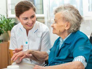 Szociális ápoló idősődő asszonyt gondoz az otthonában
