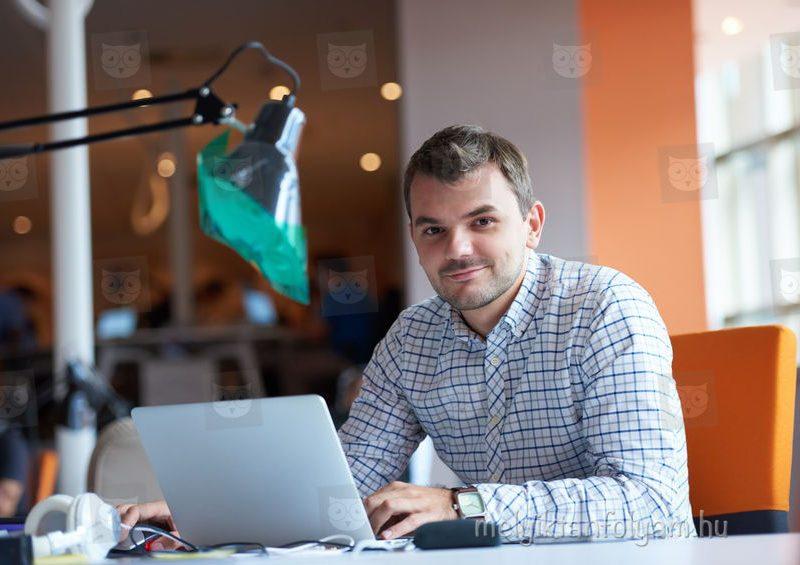 Szoftverfejlesztő munkatárs notebookján dolgozik egy informatikai cég irodájában.